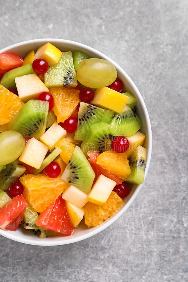 Bowl with fresh fruit salad. On grey background royalty free stock image