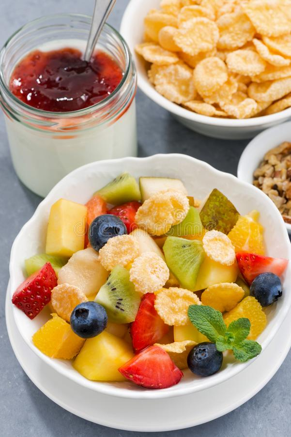 Bowl of fresh fruit salad with corn flakes, vertical closeup. Bowl of fresh fruit salad with corn flakes, closeup stock images
