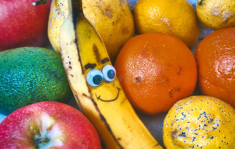 Fresh fruit with a smiley banana with a cheeky face drawn on stock image