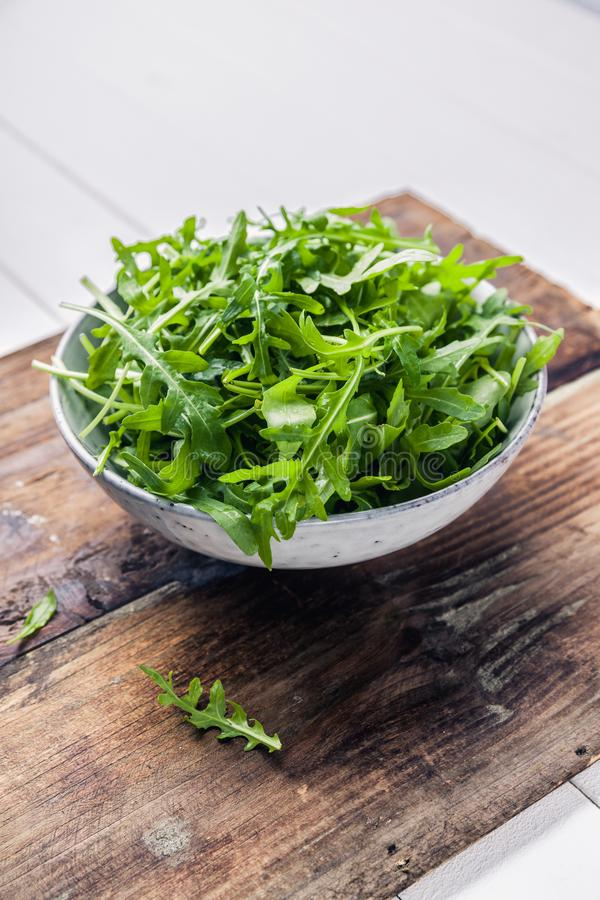 Bowl with fresh green salad arugula rucola on a wooden Black or White background stock image