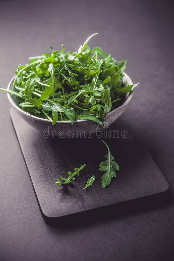 Bowl with fresh green salad arugula rucola on a wooden Black or White background royalty free stock photos