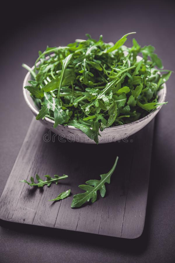 Bowl with fresh green salad arugula rucola on a wooden Black or White background royalty free stock photo