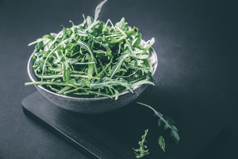 Bowl with fresh green salad arugula rucola on a wooden Black or White background royalty free stock photography
