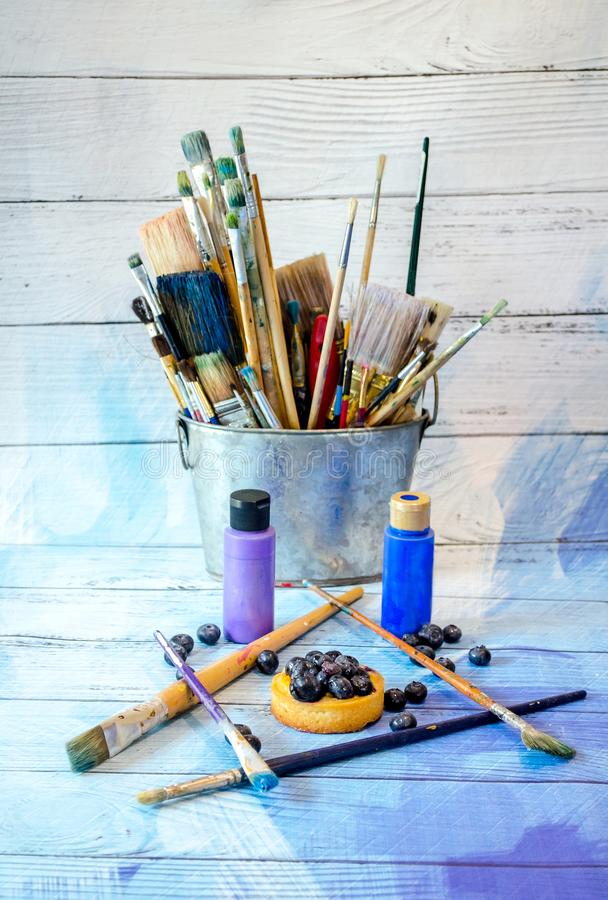Brushes and paint and the art of the beautiful blueberry royalty free stock image