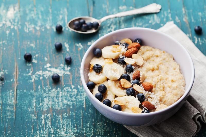 Bowl of fresh oatmeal porridge with banana, blueberries, almonds, coconut and caramel sauce on teal rustic table stock photo