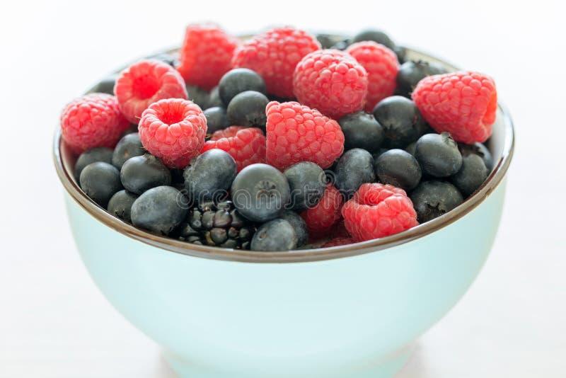 Bowl of fresh organic berries as healthy breakfast option. Bowl of fresh organic berries isolated on white background as healthy breakfast option, closeup stock photography