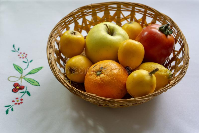 Bowl of fresh seasonal fruits. Wicker basket with summer fruits and vegetables and healthy, white, season, red, lemon, nutrition, natural, diet, apple, bananas royalty free stock photos