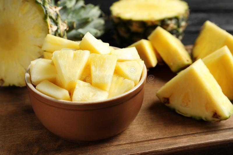 Bowl with fresh sliced pineapple. On wooden board stock photography