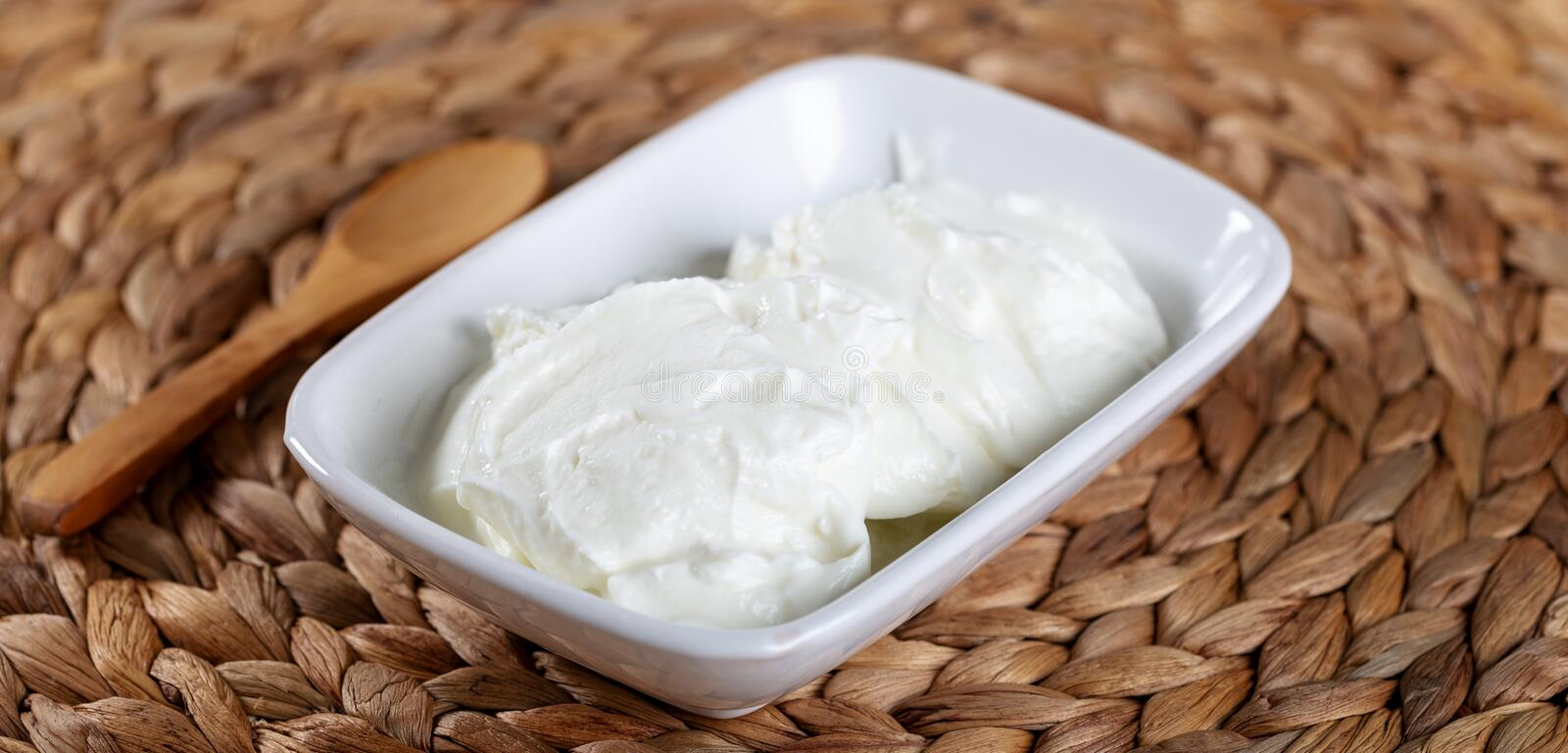 Bowl of fresh strained yogurt. Dairy product. Fresh yoghurt and wooden spoon stock photography