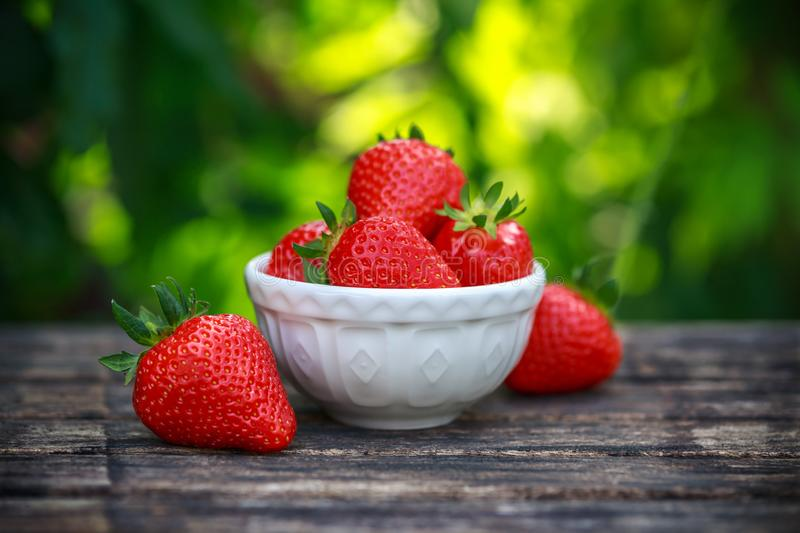 Bowl of fresh strawberries on wooden table in summer garden stock image