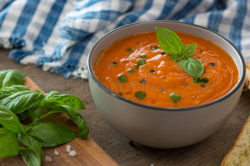 A bowl of fresh tomato soup in white ceramic bowl, garnished with basil, croutons, seasoning and a drizzle of olive oil stock photography