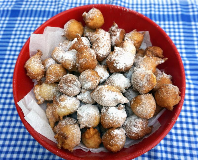 Bowl full of homemade fritters powdered with icing sugar on the vintage kitchen dish towel royalty free stock images