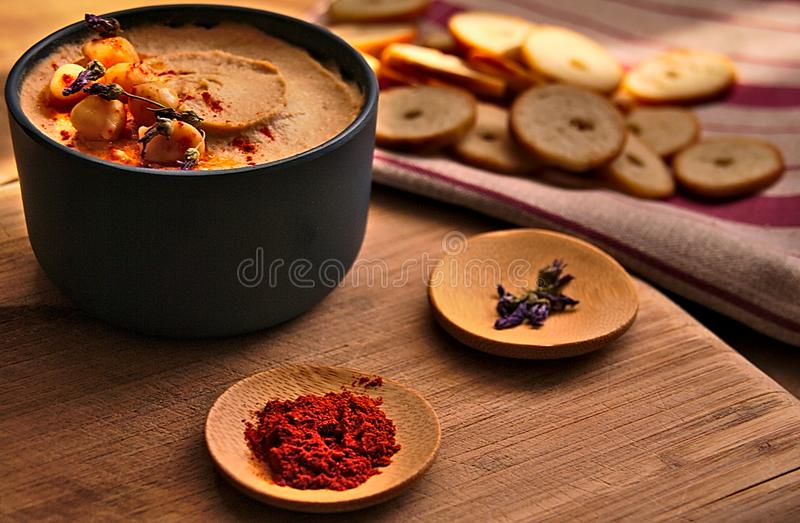 Bowl full of hummus including paprika, chickpeas, lavender and bread stock photo