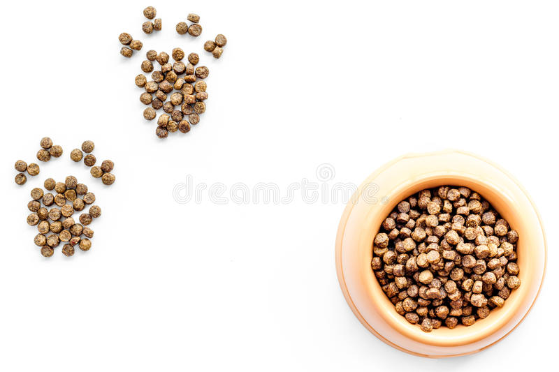Bowl full and overflowing with dry pet - dog food bits and paw prints on white background top view mock-up royalty free stock photography