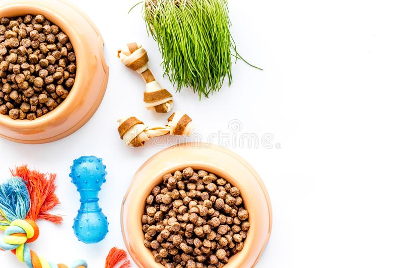 Bowl full and overflowing with dry pet - dog food bits and toys on white background top view mock-up. Orange plastic bowl full and overflowing with dry pet - dog royalty free stock images