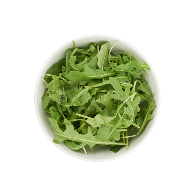 Bowl full of rocket salad leaves isolated. Ceramic bowl full of rocket salad leaves isolated over the white background, top view above royalty free stock photos