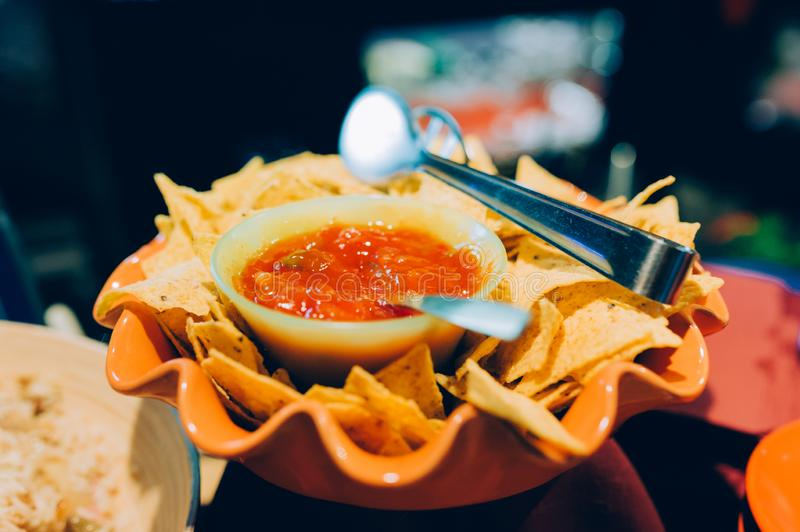 Bowl full of yellow mexican nachos chips with hot spicy red sauce inside bar with artificial  light and spoon served as appetizer stock photo