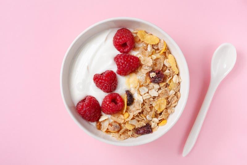 Bowl with greek yogurt, raspberries and muesli on pink table top view. Healthy diet breakfast royalty free stock photo