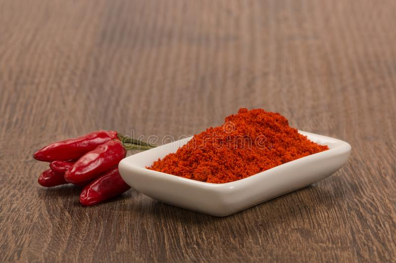 Bowl of ground red pepper spice in bowl over wood background stock photography