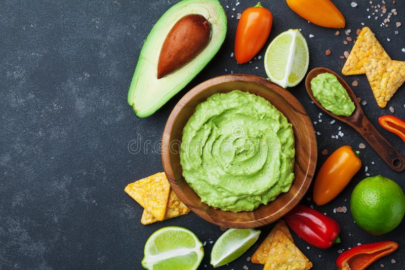 Bowl guacamole with avocado, lime and nachos top view. Mexican food. Bowl guacamole with avocado, green lime and nachos top view. Mexican food royalty free stock photo