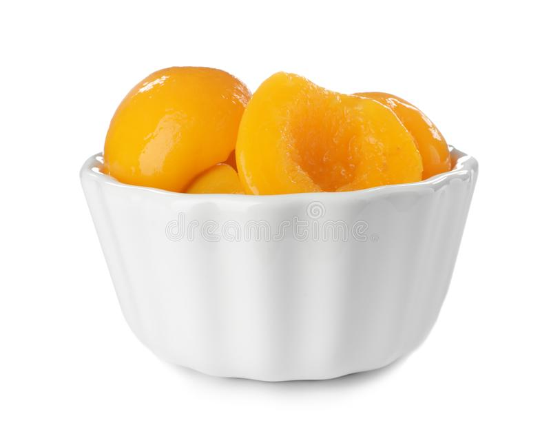 Bowl with halves of canned peaches. On white background royalty free stock photography