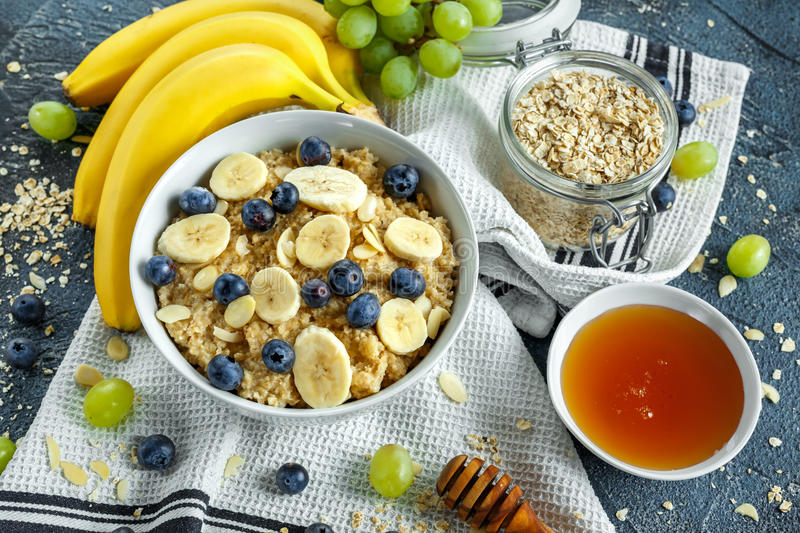 Bowl of Healthy Breakfast oatmeal with ripe blueberries, banana, honey, almonds and green grape. Top view stock photo