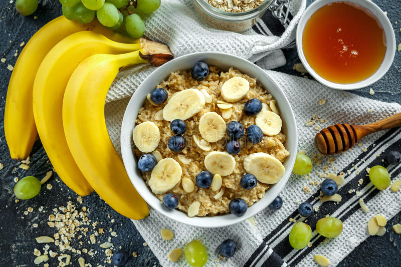 Bowl of Healthy Breakfast oatmeal with ripe blueberries, banana, honey, almonds and green grape. Top view stock image