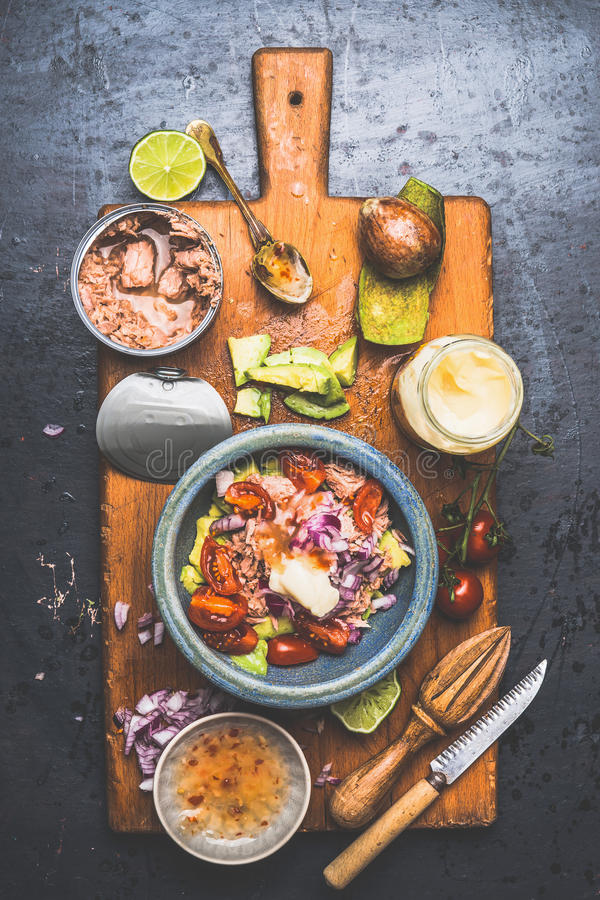 Bowl with Healthy canned Tuna fish salad ingredients : avocado, tomatoes and lime on rustic cutting board and dark background royalty free stock image