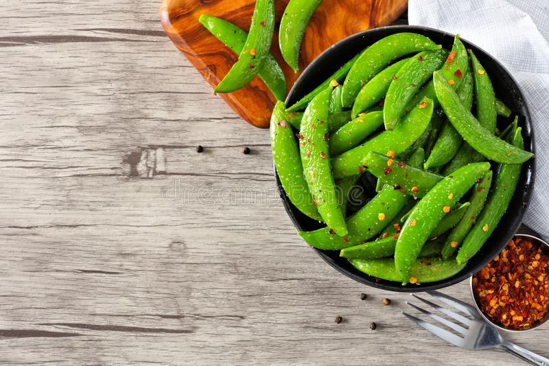 Bowl of healthy roasted snap peas. Top view with copy space on wood. Bowl of healthy roasted snap peas. Top view, corner orientation with copy space on a wood royalty free stock photos