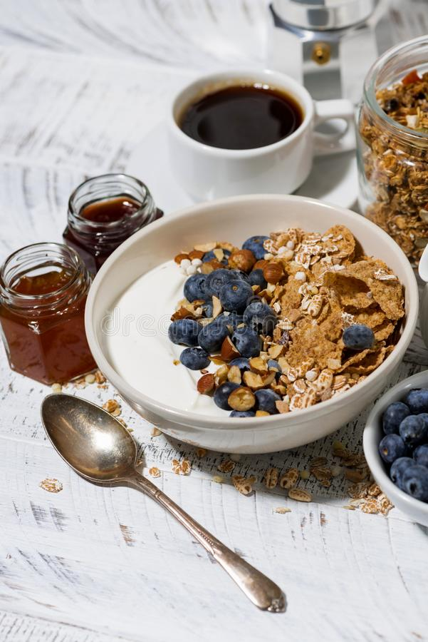 Bowl of healthy wholegrain flakes, natural yogurt and fresh blueberries for breakfast, vertical stock photo