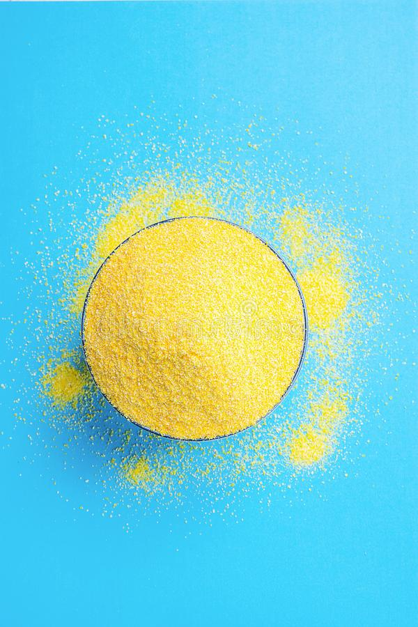Bowl with Heap of Dry Uncooked Vibrant Yellow Color Polenta Spilled on Light Blue Background. Top View. Creative Image. stock photo