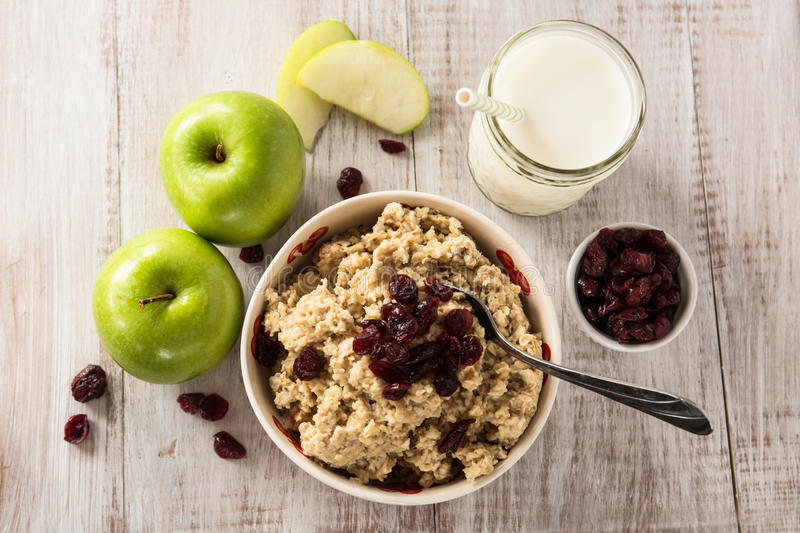 Bowl of Heart Healthy Breakfast Oatmeal With Fruit. Bowl of heart healthy breakfast oatmeal with apples and cranberries and glass of milk royalty free stock photo