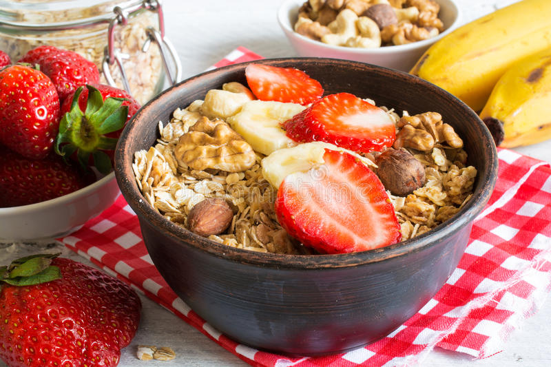 Bowl of homemade fruit muesli with strawberry, banana and nuts royalty free stock photography