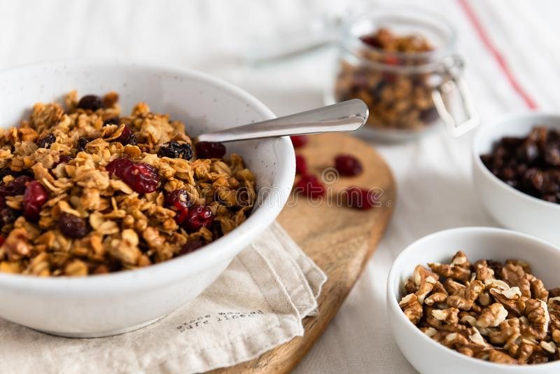 Bowl of homemade granola with nuts and fruits on white linen background. Side view, copy space. Healthy breakfast concept stock images