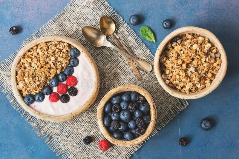 Bowl of homemade granola with yogurt and fresh berries blueberries and raspberries on blue rustic background. Healthy diet royalty free stock images