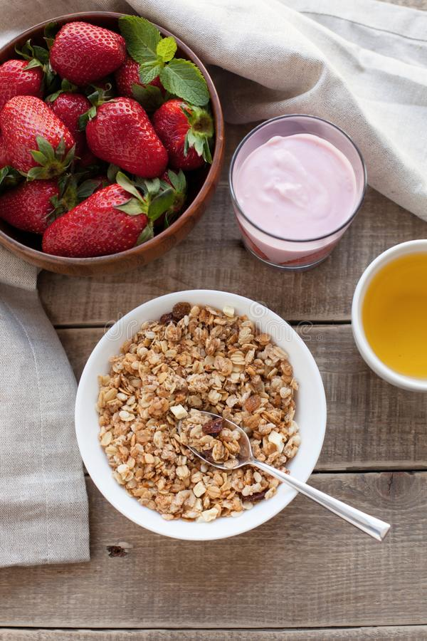 A bowl of homemade granola with yogurt and fresh strawberries on a wooden background. Healthy breakfast with green tea.  stock image