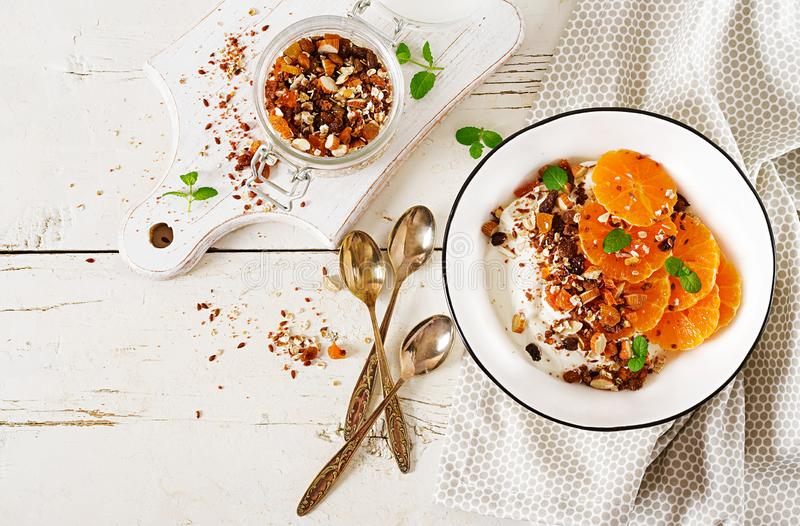 Bowl of homemade granola with yogurt and tangerine on white wooden table. Fitness food. Top view stock photography