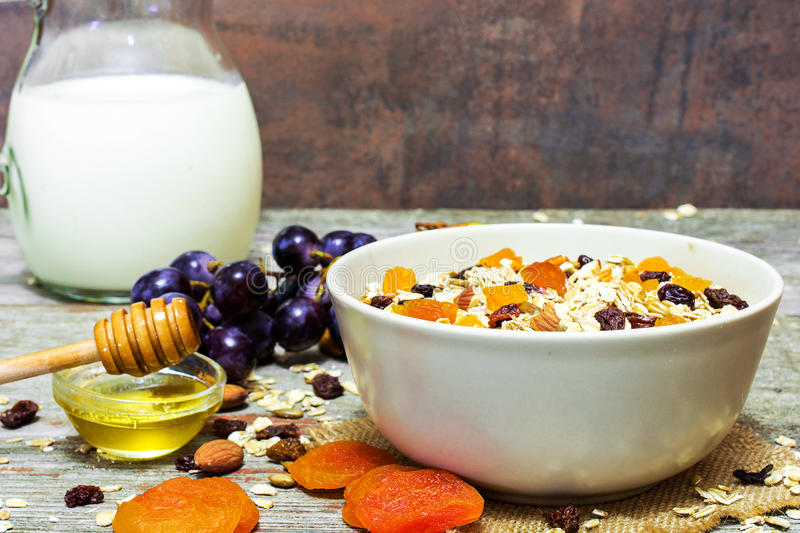 Bowl of homemade muesli with nuts, dried fruits, honey royalty free stock photography