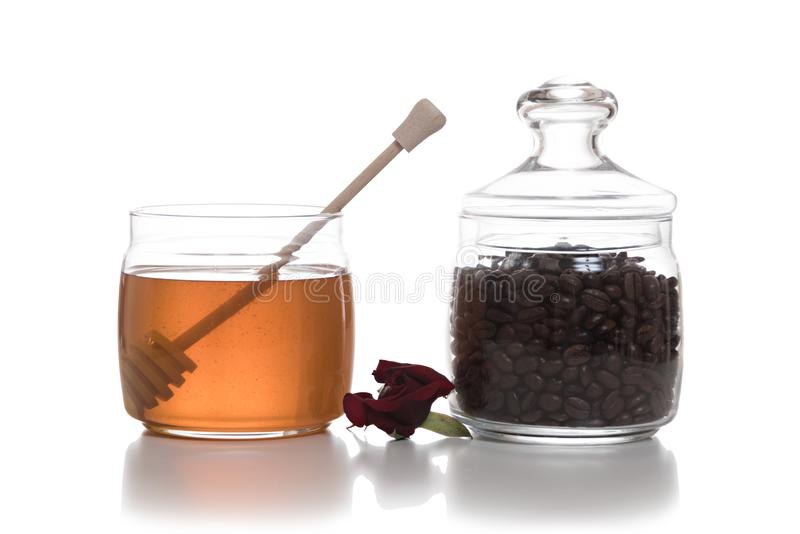 Bowl of honey next to a jar of coffee beans stock images