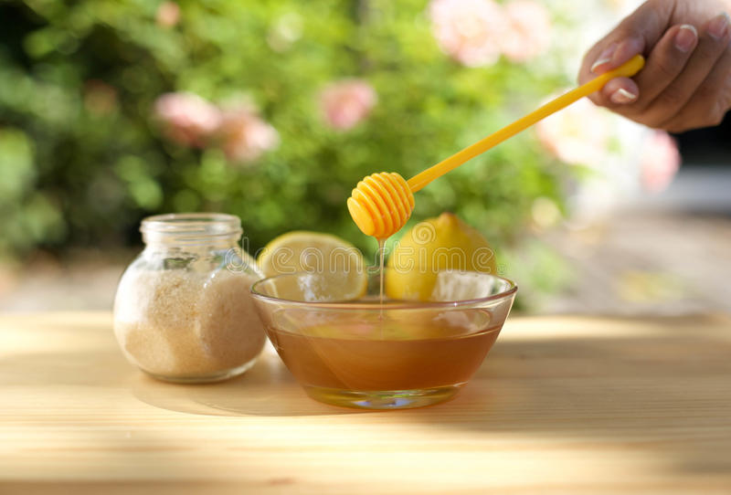 Bowl of honey and sugar and lemons on wooden table royalty free stock image