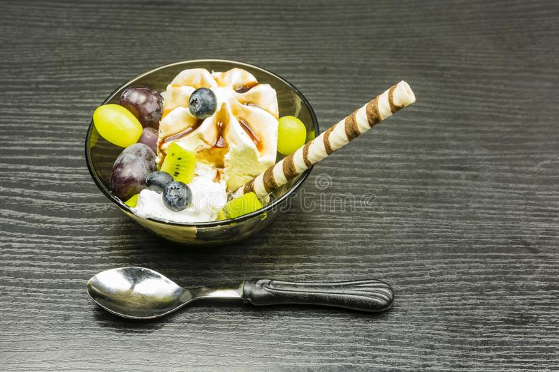 A bowl of ice cream with whipped cream, chocolate and fresh fruit. royalty free stock photos