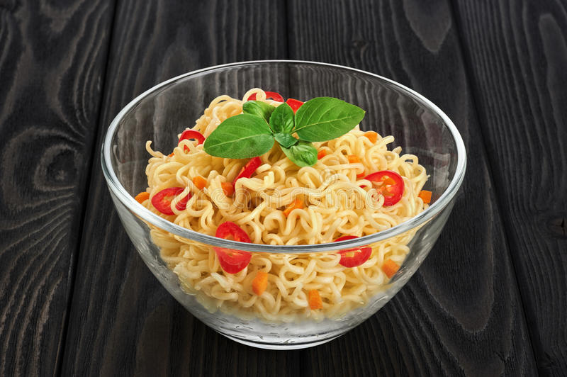 Bowl of instant noodles with basil and chili on a dark backgroun stock photo
