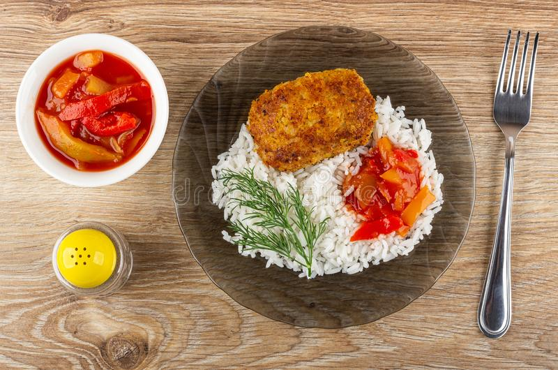 Bowl with lecho, pepper shaker, brown plate with fried patty, rice, lecho, dill, fork on table. Top view. Bowl with lecho, pepper shaker, transparent brown plate stock photos