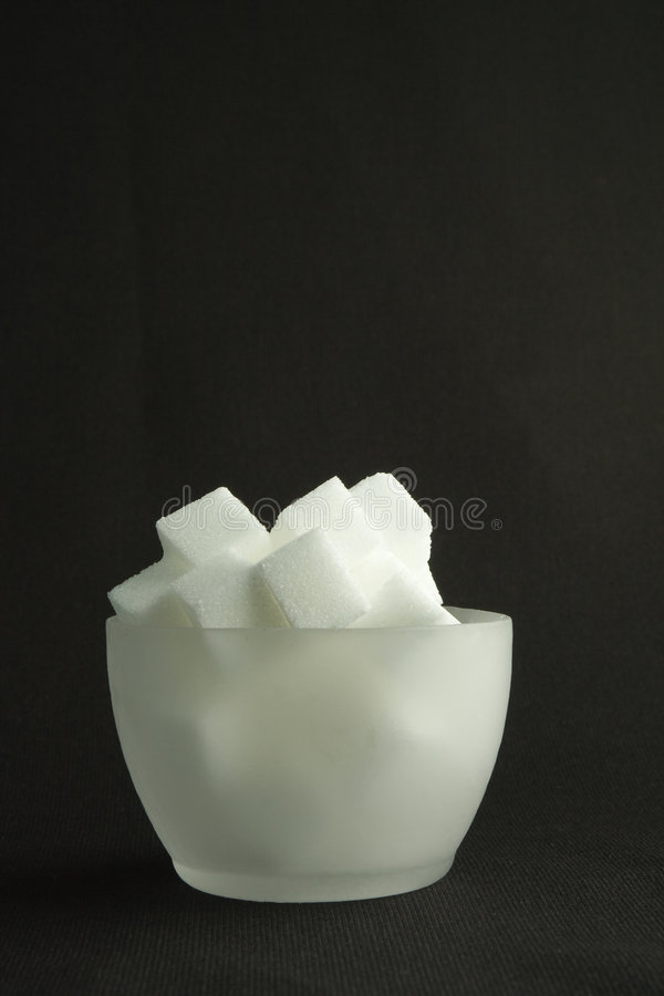 Bowl Lump Sugar. A translucent bowl of white lump sugar, on a black background royalty free stock image