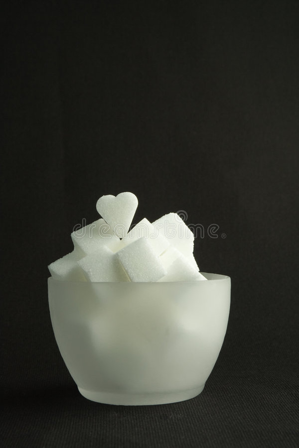 Bowl Lump Sugar. A translucent bowl of white lump sugar, on a black background royalty free stock images