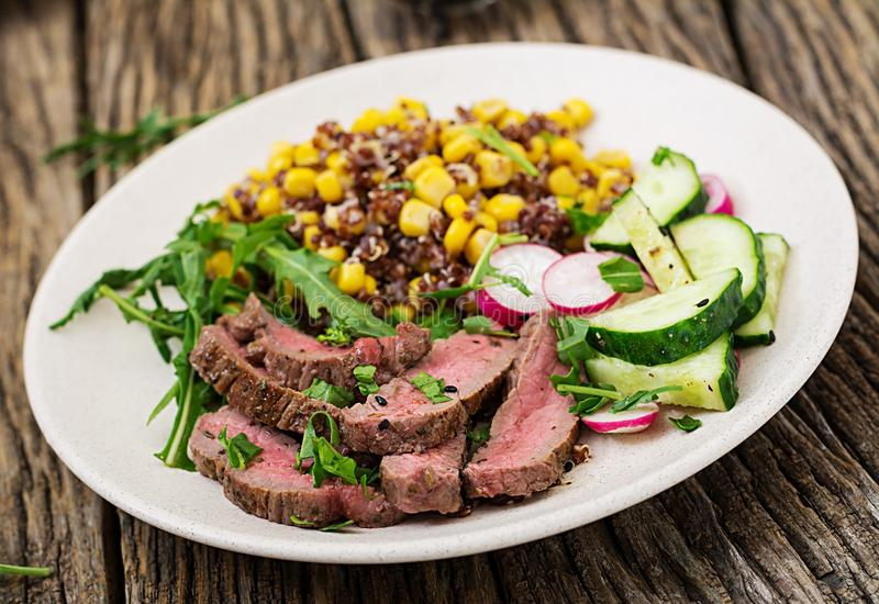Bowl lunch with grilled beef steak and quinoa, corn, cucumber, radish and arugula. Healthy dinner. Bowl lunch with grilled beef steak and quinoa, corn, cucumber royalty free stock images