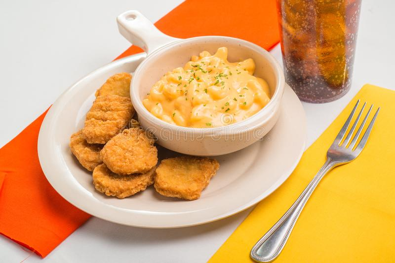 A bowl of Macaroni and cheese served with a side of Chicken Nuggets royalty free stock photo