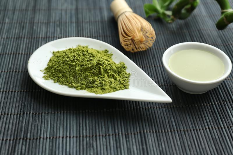 Bowl of matcha tea and plate with powder on bamboo mat stock photo