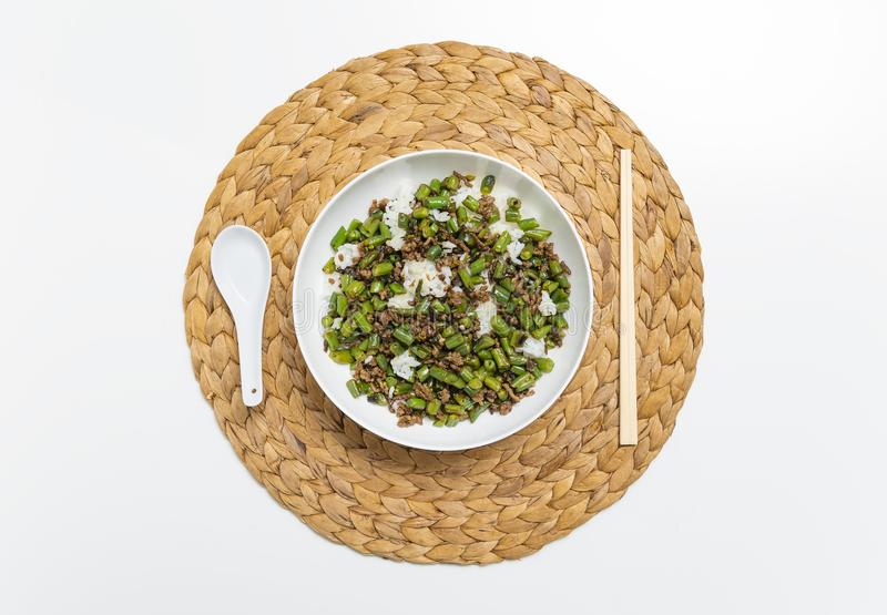 Bowl of minced beef with round beans and rice, with chopsticks and spoon on straw mat stock image