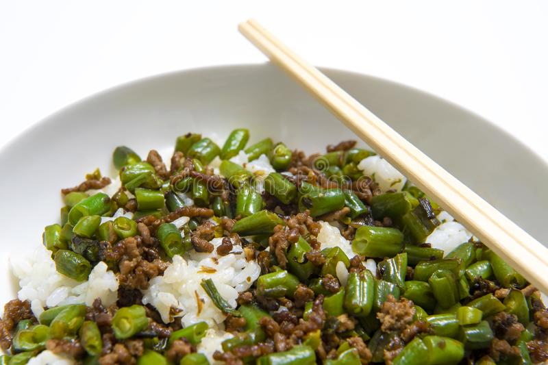 Bowl of minced beef with round beans and rice, with chopsticks on white background royalty free stock images